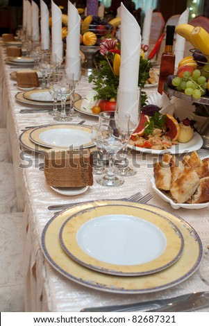 Row of plates and appetizers on a banquet table with shallow depth of field - stock photo