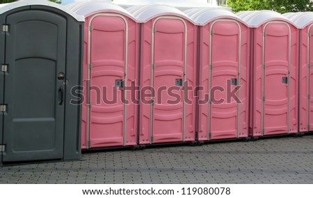 Row of portable grey and pink toilets - stock photo