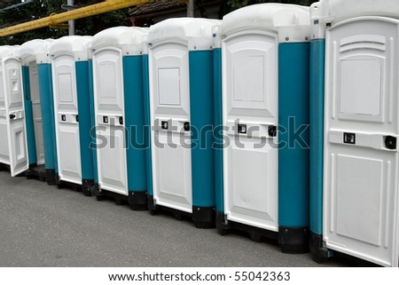Row of portable toilets at an outdoor event - stock photo