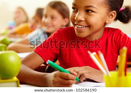 Row of pupils looking at teacher with cute girl in front - stock photo