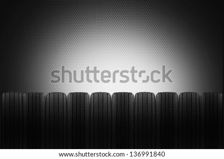 row of radial and cross ply rubber tyres to make background for a tyre sales garage - stock photo