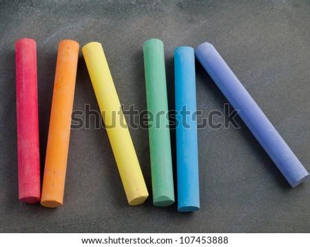 row of rainbow colored chalk on a blackboard - stock photo