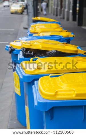 Row of recycling bins on roadside with waste to be collected - stock photo