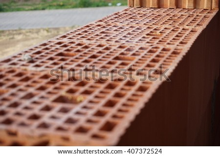 Row of red bricks with the inner holes in the shape of honeycomb on the construction site