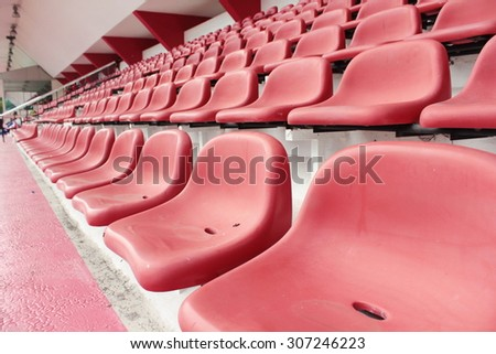 row of red seat in football stadium in perspective