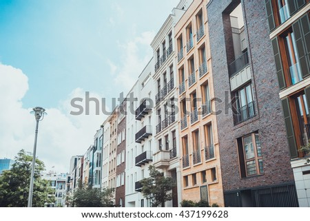 Row of residential apartment buildings in city under partly cloudy sky with trees and street light in foreground - stock photo