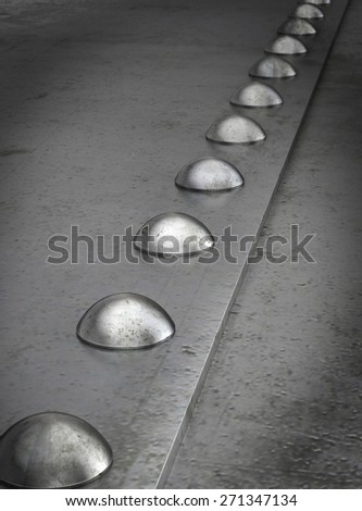 Row of rivets on the metal grunge background - stock photo