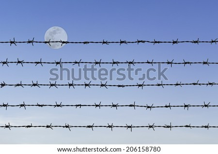 row of rustic barbed wire over abstract full moon sky background - stock photo