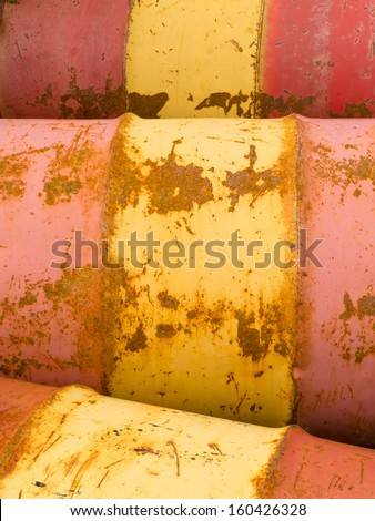 Row of rusty steel metal oil barrels yellow and red petroleum energy industry background texture pattern abstract - stock photo