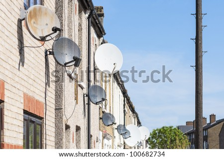 Row of satellite dishes installed in front of brick houses. - stock photo