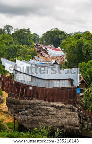 Row of scenic buildings in traditional village, with typical boat shaped roofs, set amid lush green rainforest. Mamasa region, West Tana Toraja, South Sulawesi, Indonesia. - stock photo