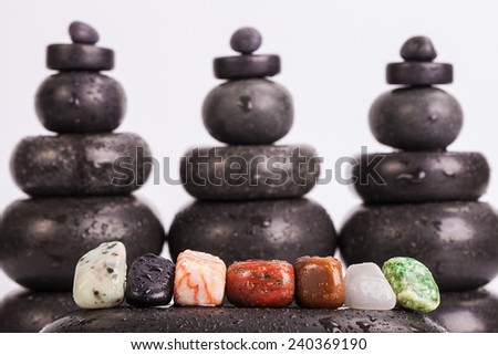 Row of seven chakra colored crystals lined in a row on wet smooth polished hot massage black stone with a blurred backgrounds from hot massage black stones - stock photo