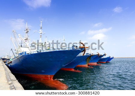 Row of ships docked at harbor - stock photo