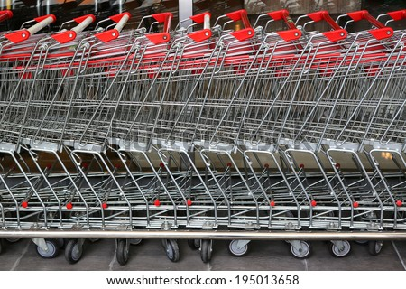 row of shopping trolleys or carts in supermarket - stock photo