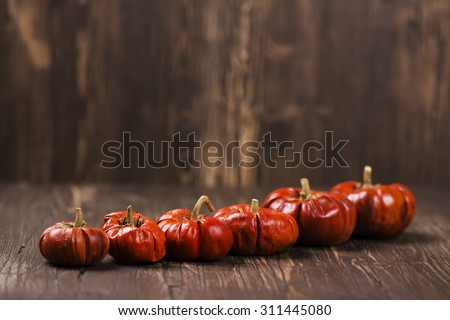 Row of small decorative pumpkins. Halloween or thanksgiving day concept. Vintage style, selective focus - stock photo