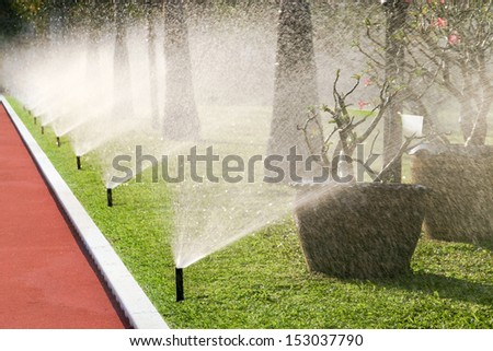 Row of sprinkler heads watering the grass  - stock photo