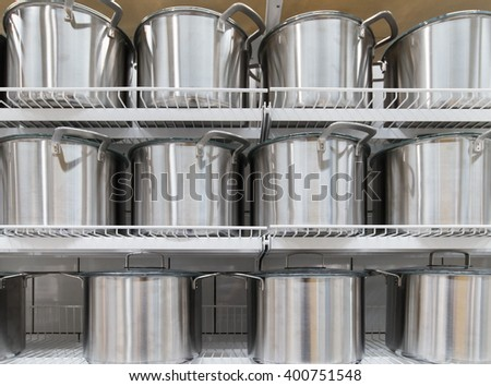 row of stainless pot on a shelf - stock photo