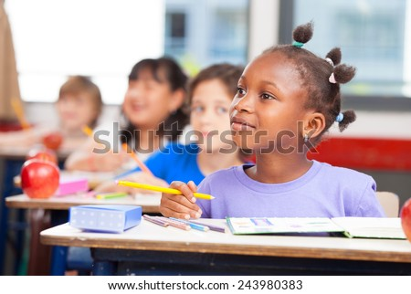 Row of students in a primary interracial classroom. Afro american girl paying attention to the teacher.