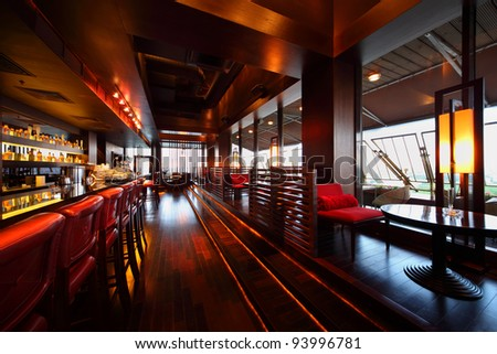 Row of tables, red seats and bar counter with red tall chairs in empty cozy restaurant - stock photo