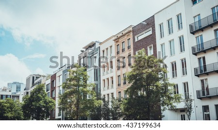Row of tall leafy green deciduous trees in front of upscale residential apartment buildings under partly cloudy summer sky - stock photo