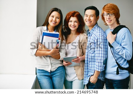 Row of teenage friends looking at camera in college - stock photo