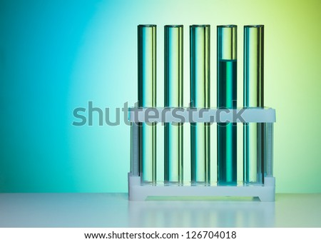 Row of test tubes in laboratory on blue background with laboratory light - stock photo