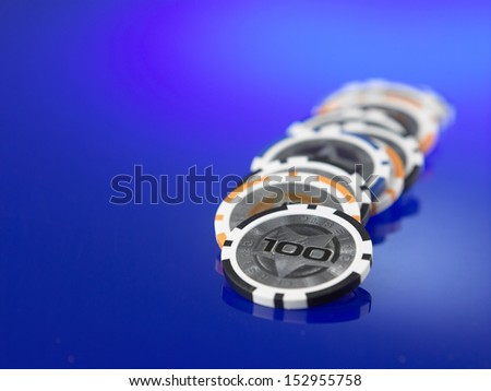 row of the casino chips on the blue background - stock photo