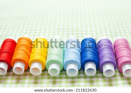 row of thread spools in rainbow colors, skein collection, top view - stock photo