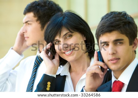 Row of three agents calling by their mobile phone