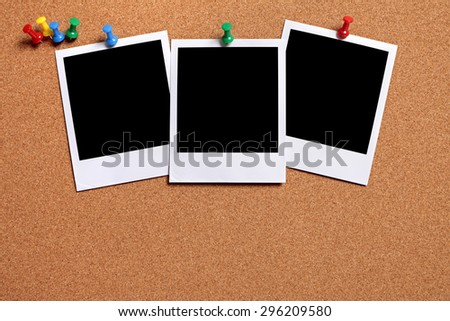 Row of three blank polaroid frame photo prints, cork notice board.  Copy space. - stock photo