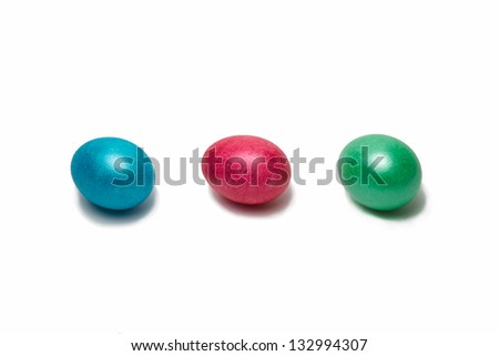 Row of three Easter eggs of blue, red and green color isolated against the white background