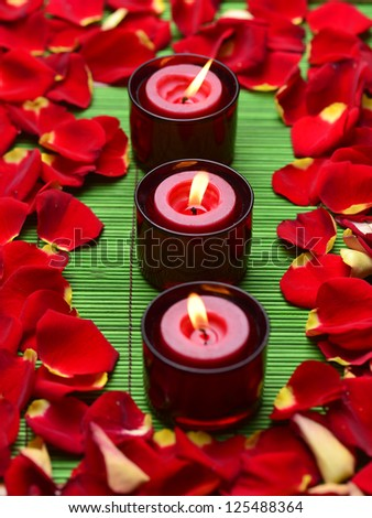 Row of three red candles with rose petals