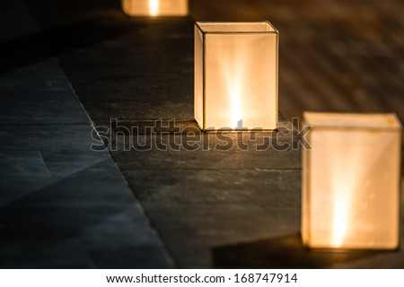 Row of three square lanterns with dim light standing on stone floor. Focus on central lantern. Street decoration and lighting. Warm and romantic atmosphere of evening. - stock photo