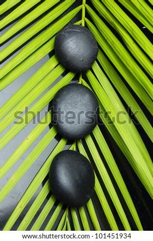 Row of three zen stone on palm leaf texture - stock photo
