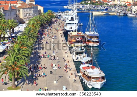 Row of tourist boats by the pier in the harbor of Trogir, Croatia - stock photo
