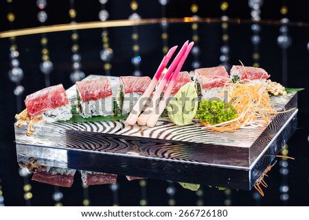 Row of tuna sushi rolls with wasabi and ginger - stock photo
