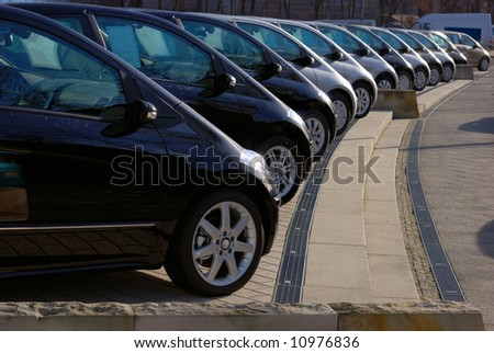 row of twelve grey and black cars displayed for sale