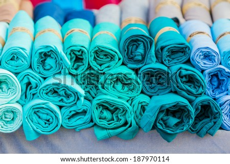 Row of variety multicolored shirt clothes hanging on shelf outdoor for sale, no brandnames or copyright objects.  - stock photo