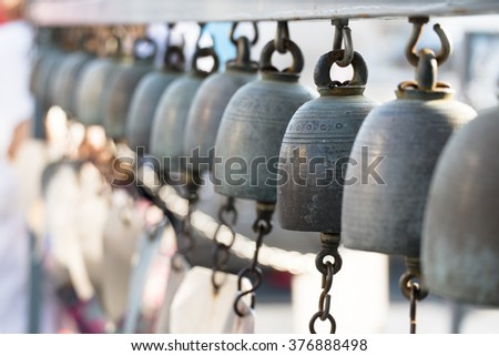 Row of vintage brass bells in buddist temple at Thailand.