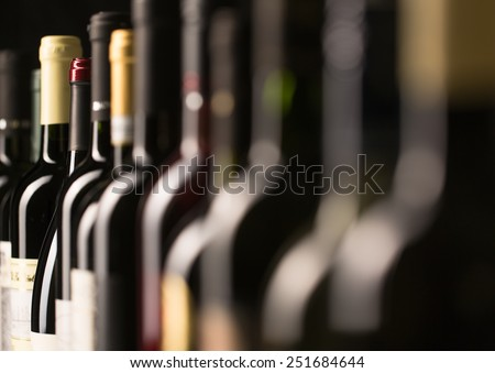 Row of vintage wine bottles in a wine cellar (shallow DOF; color toned image) - stock photo