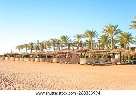 Row of wattled straw umbrellas on sunny summer tropical beach. Egypt. Sharm-el-sheikh. Outdoors. - stock photo