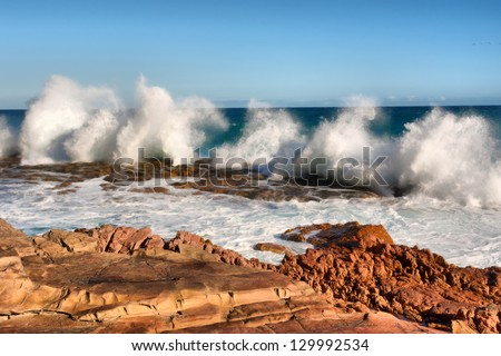 Row of wave splashes on red rock beach. Shot in the Cape of Good Hope and Cape Point Nature Reserve, Table Mountain National Park, near Cape Town, South Africa. - stock photo