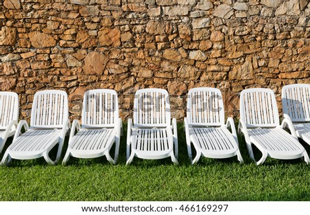 Row of white plastic sun loungers