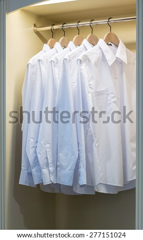row of white shirts hanging on coat hanger in wardrobe - stock photo