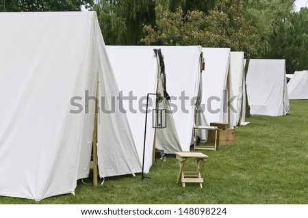 Row of white tents in Union camp at reenactment of American Civil War (1861-1865), Four Seasons Park, Lombard, Illinois, on July 27, 2013. Typically, the volunteer actors sleep in such tents at night. - stock photo