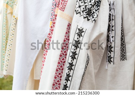 Row of white textile shirts with colored ethnic folk patterns  - stock photo