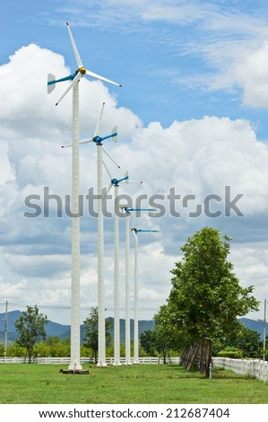 row of wind turbine and tree on grassland against cloud and blue sky - stock photo