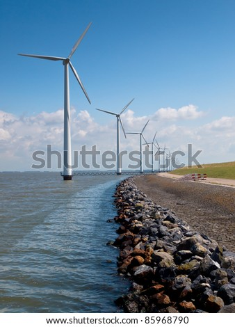 Row of wind turbines along the coast - stock photo
