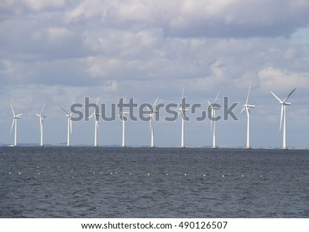 Row of wind turbines at sea on an overcast day. Shot near Copenhagen, Denmark.