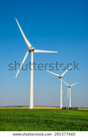 Row of wind turbines in a field - stock photo